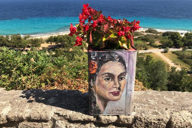 ART: A painted feta cheese tin used as a flower pot in Athitos