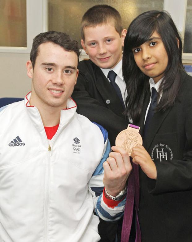 Kristian Thomas shows his bronze Olympic medal to Dawid Jedryszczak, aged 12, and Haania Hussain, aged 11. Buy photo: 521210J