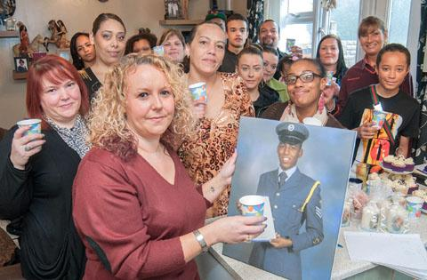 Godmother Maxine Taylor with a photo of Junior in his cadet uniform, with his mum, Jennifer Wright, centre, and his friends and family. Buy photo: 111313MH