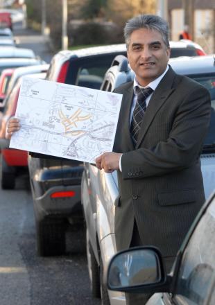 Dudley Cllr Khurshid Ahmed says the answer to parking problems near Russells Hall hospital may be paid for residents' permits but politcal opponants have slammed the idea