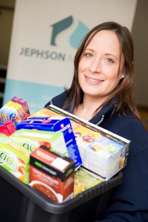 Keira Lymath with a box of long-life foods and toiletries ready to be donated to a foodbank.