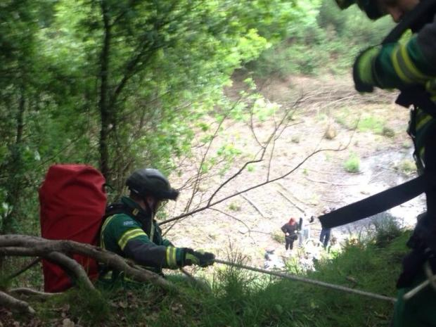 Paramedics used ropes to lower themselves down to treat the patient.