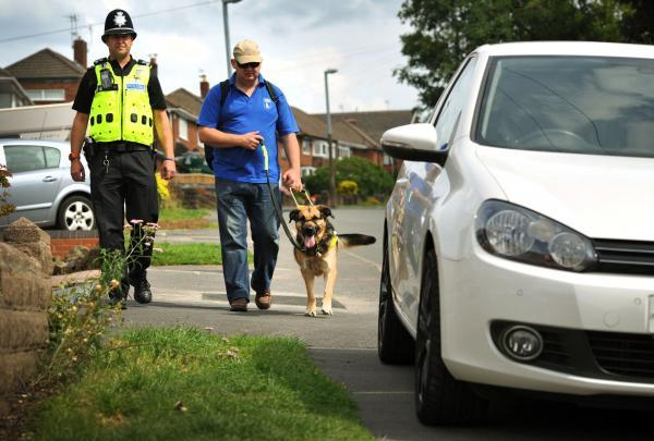 Sgt Richard Cruickshank with Karl Denning and his dog Quasia approach a car parked on the pavement in Brownswall Road Sedgley.