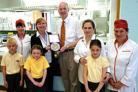 Headteacher David Baker, dinner ladies and pupils from Roberts Primary receive their award from Julia Simmonds.