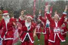 People dressed as Santa Claus brave the rain and cold during the Santa Dash at Clapham Common (Victoria Jones/PA)