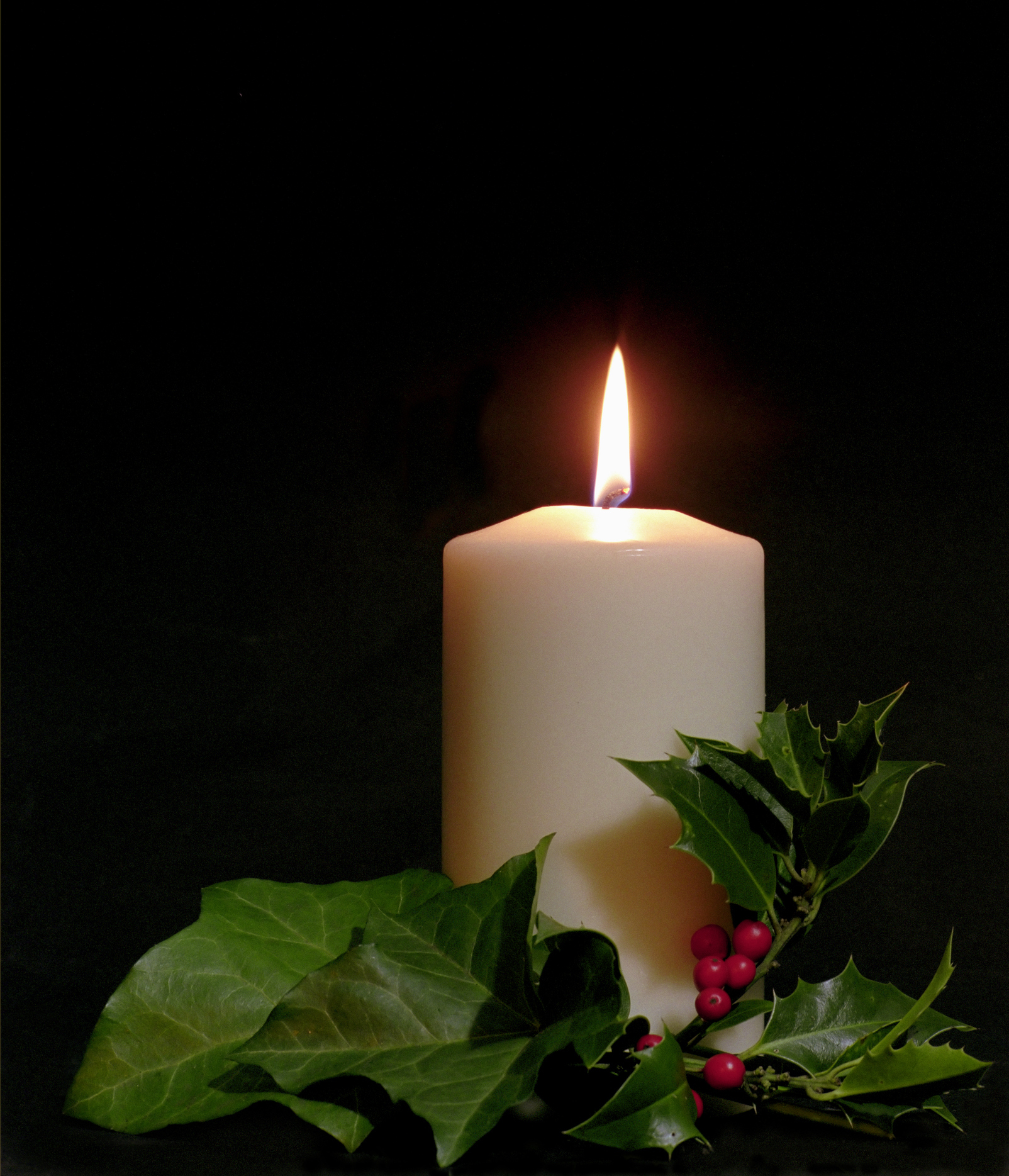 Burning candle surrounded by holly and ivy leaves, traditional christmas plants.