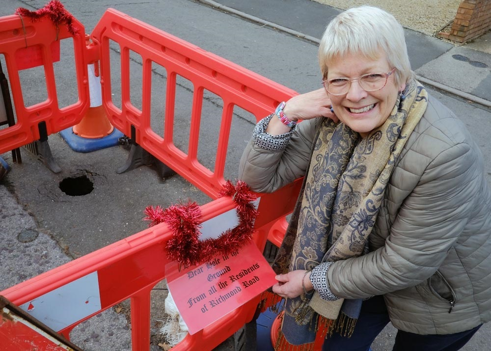 Pauline Geddie has hung Christmas decorations on roadworks which she says have been left in Richmond Road since May