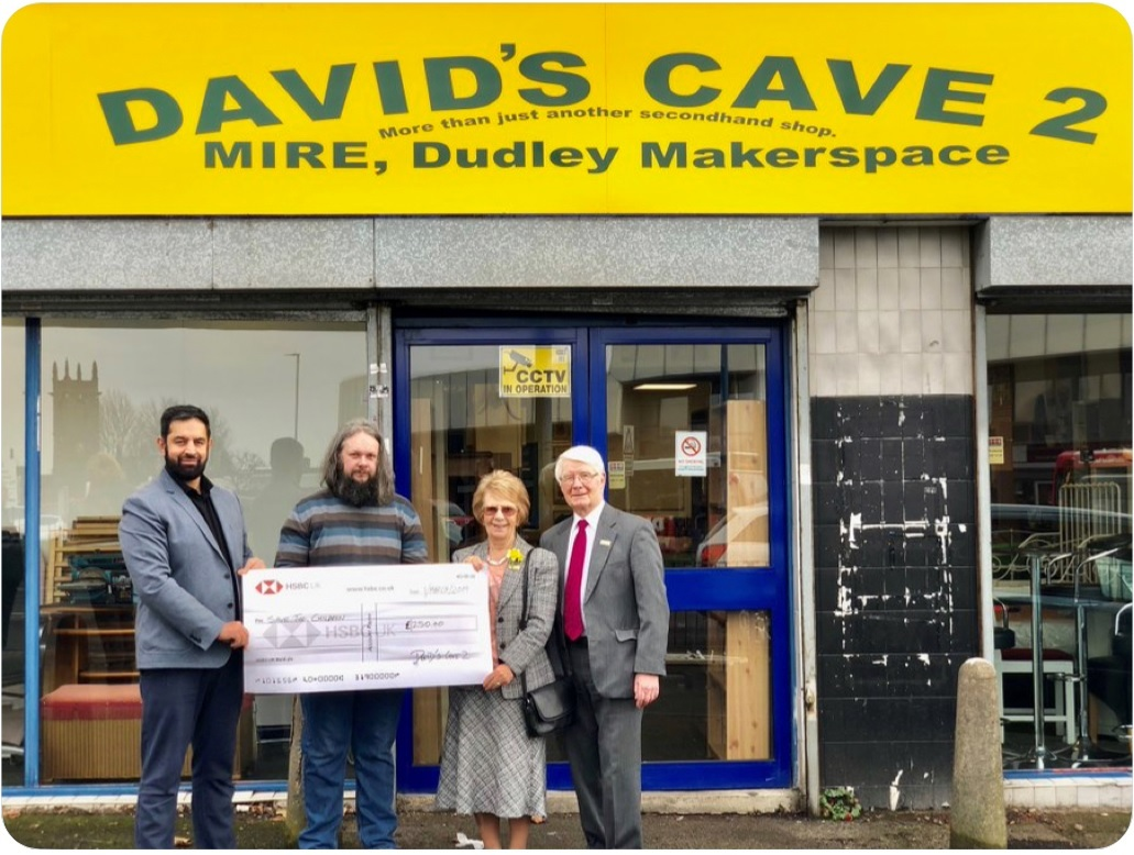 David Pils of Dave's Cave and Dudley town ambassador Mohammed Sagir hand over donations to Save the Children outside the new Trindle Road shop.